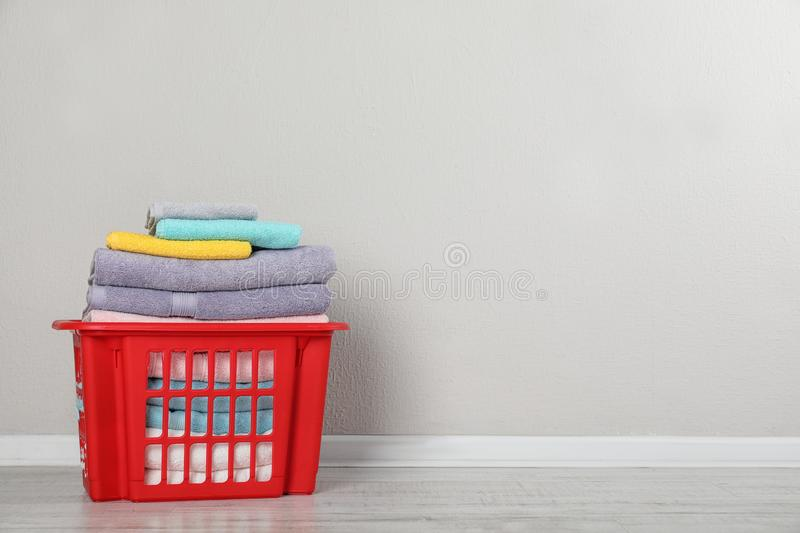 Laundry basket with clean towels on floor near light wall. Space for text stock image