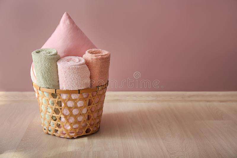 Laundry basket with clean towels and pillow on floor near color wall stock photos