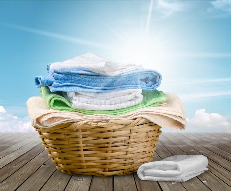 Laundry Basket with colorful towels on background stock photo