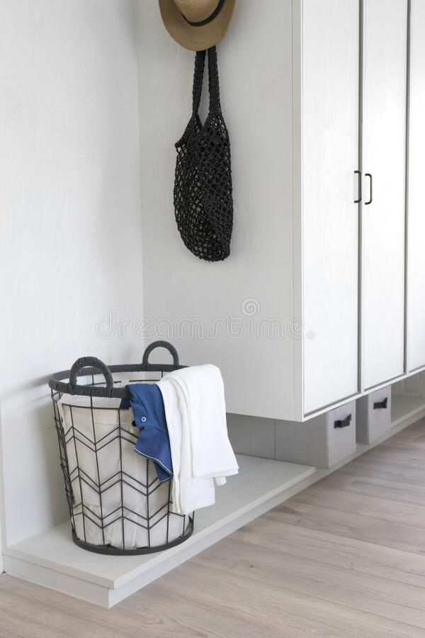 Laundry basket with dirty clothes in room corner. stock image