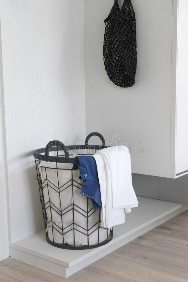 Laundry basket with dirty clothes in room corner. royalty free stock photos