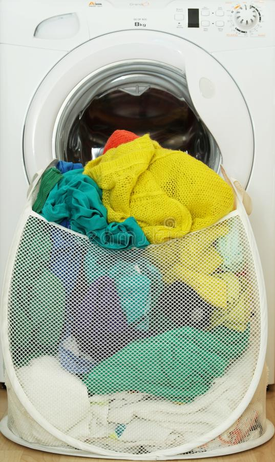 Laundry basket full of dirty clothes. Standing next to washing machine royalty free stock photography