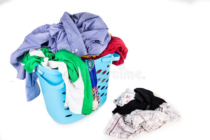 Laundry basket full of worn apparels for washing against white background stock image