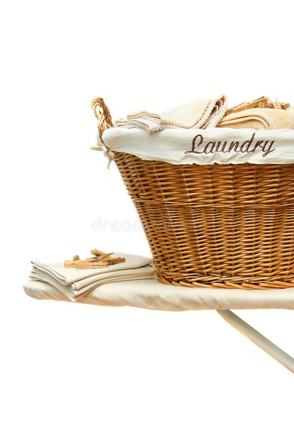 Laundry basket on ironing board against white. Laundry basket with towels on ironing board against white background stock image