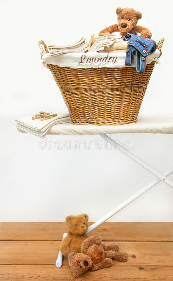 Laundry basket with teddy bears on floor royalty free stock photos