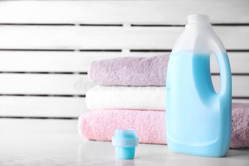 Laundry detergent and clean towels on table against blurred background. Space for text stock image