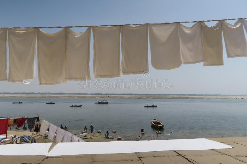 Laundry drying at string at the border of river Ganges stock image
