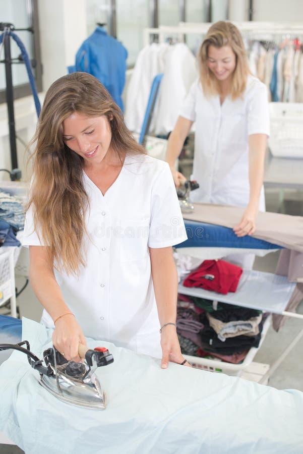 2 laundry employees smiling while ironing. 2 royalty free stock image