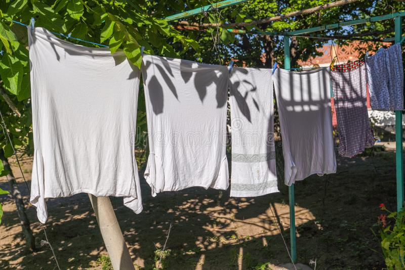 Laundry hanging out to dry outdoors in summer under sun, under tree partly shadow royalty free stock images