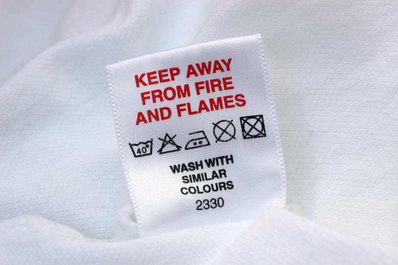 Laundry Label. Keep away from fire laundry label. With machine wash 40 degrees, do not bleach, medium iron, do not dry clean and do not tumble dry symbols stock photo