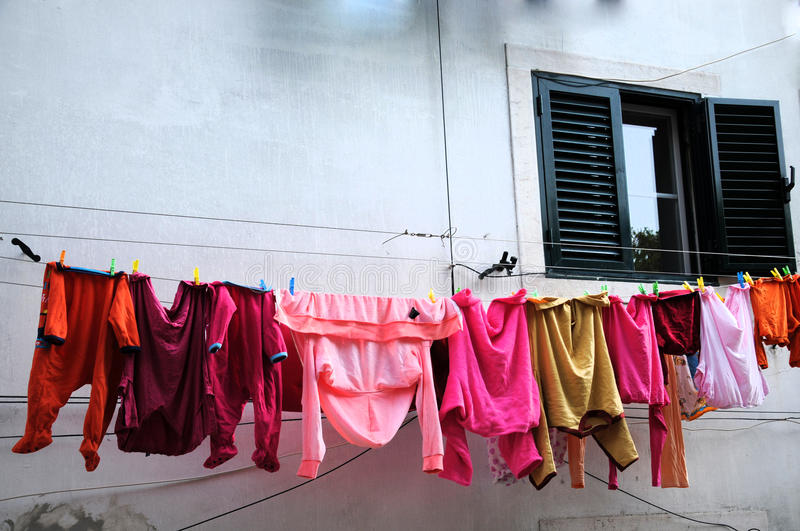 Laundry in pink. Colorful clothes drying outside at a line between the windows stock photo