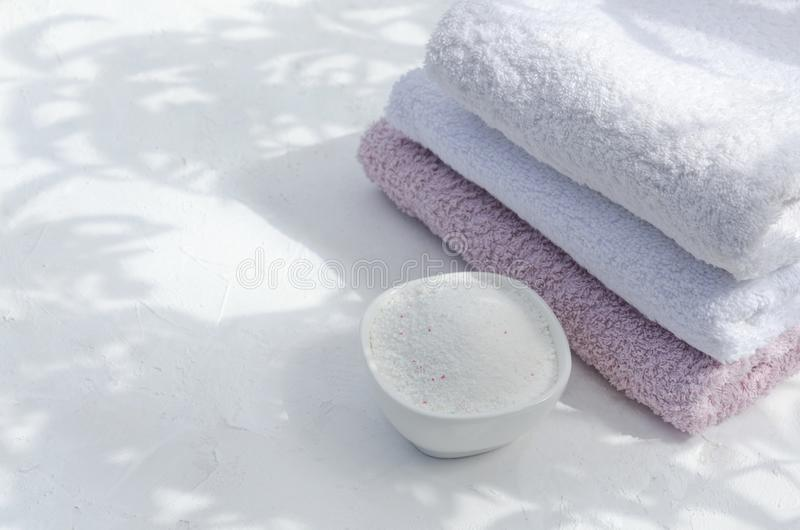 Laundry powder, clean towels on the white surface.Natural ligth, shadows.Empty space for text. Powder, stack of clean towels and blank cleaning listce stock images