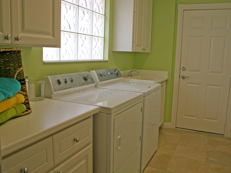 Laundry Room. Clean and attractive laundry room with white appliances and cabinets, lime green walls, basket of colorful towels and tiled floor