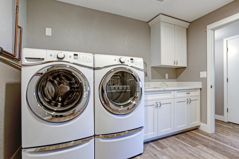Laundry room with taupe walls and modern appliances. royalty free stock photos
