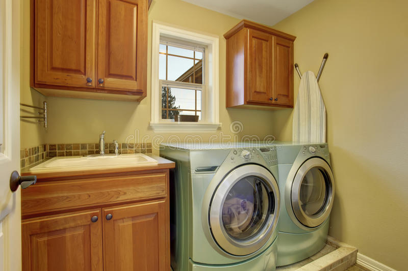 Laundry room with washer and dryer. Wooden cabinets and sink. Laundry room with washer and dryer. Wooden cabinets and tile floor stock photos
