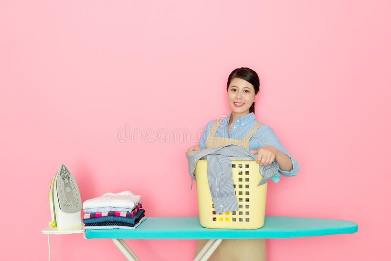 Laundry store worker standing in pink background royalty free stock images