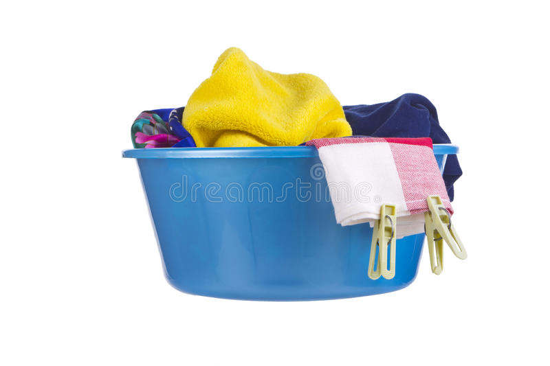 Laundry - wash-basin with clothes. Laundry - blue wash-basin with clean clothes and clothespins royalty free stock images
