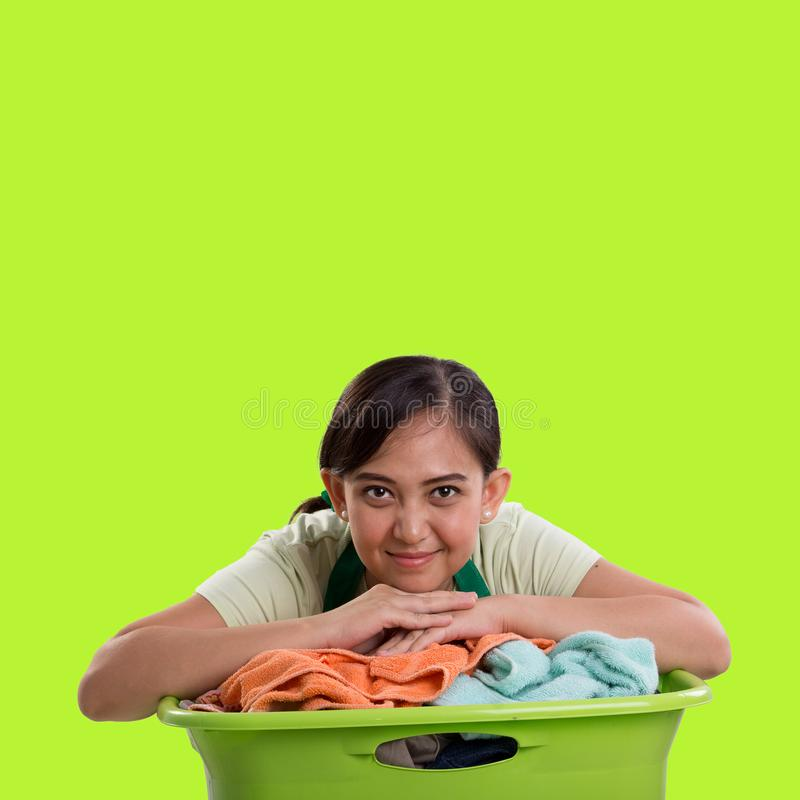 Laundry woman over green background. Asian housemaid resting on top of laundry basket, isolated over green background for design copyspace stock image