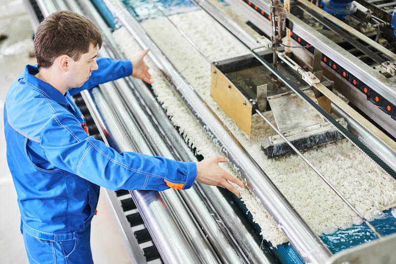 Laundry worker in the process of working on automatic machine for carpet washing. In dry cleaning stock photography