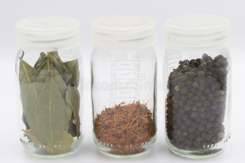 Laurel de bahía, azafrán y pimienta negra en contenedores de almacenamiento foto de archivo libre de regalías