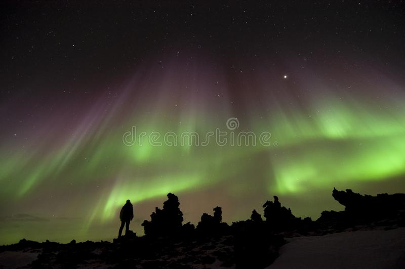 Viking human silhouette alone contemplating northern lights spectacle on rocky lava field stock image