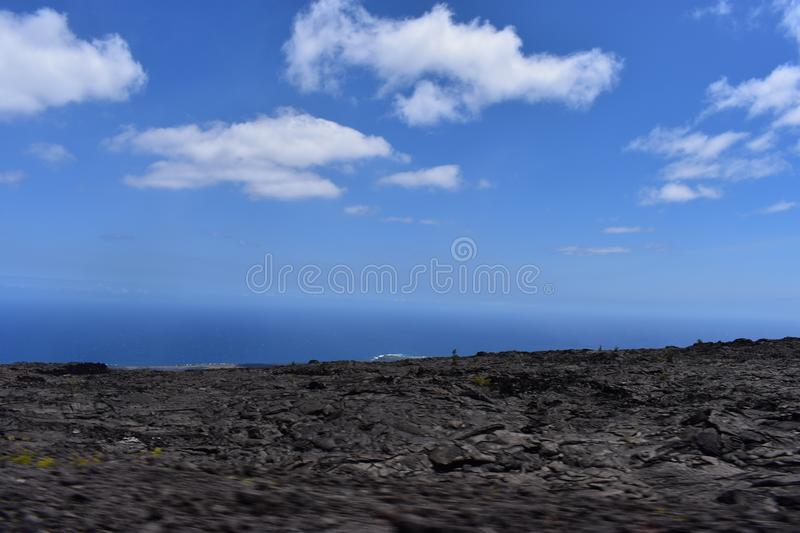 Lava fields on the Big Island in Hawaii with the Pacific Ocean in the background stock photography