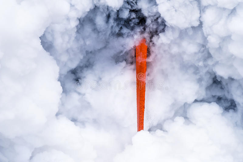 Lava flow in Hawaii. A lava flow on the big Island of Hawaii known as the fire hose spews out molten magma from Kilauea Volcano into the ocean, causing stock image