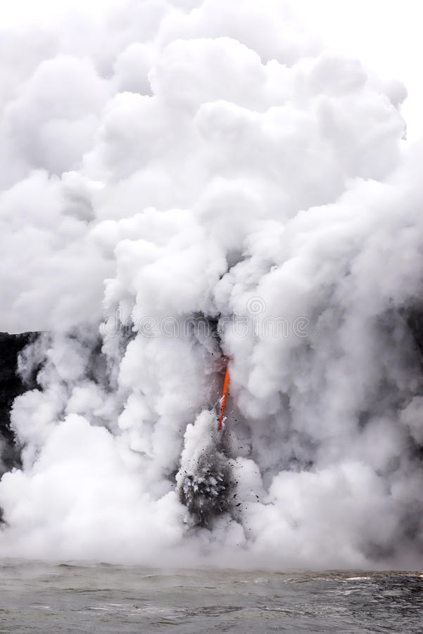 Lava flow in Hawaii. A lava flow on the big Island of Hawaii known as the fire hose spews out molten magma from Kilauea Volcano into the ocean, causing royalty free stock photos
