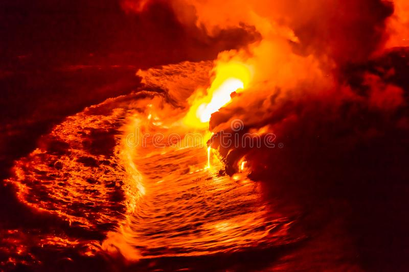 Lava flow pouring into Hawaii ocean at night royalty free stock photo