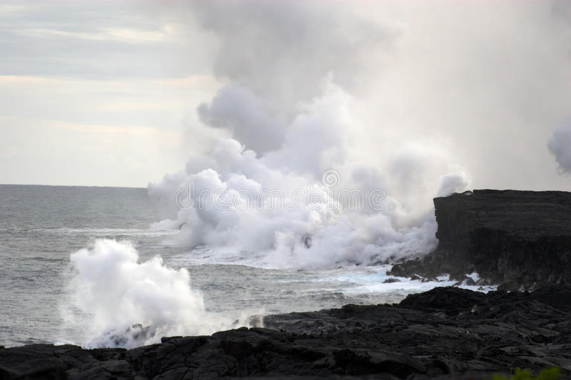 Lava flowing into the ocean. Lava erupting into Pacific Ocean during day on Big Island stock images