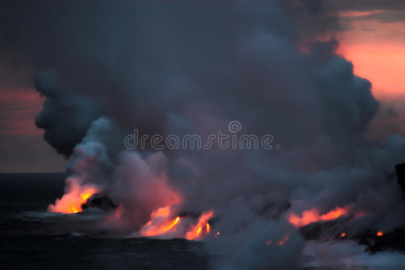 Lava flowing into the ocean. Lava erupting into Pacific Ocean at night on Big Island royalty free stock photos