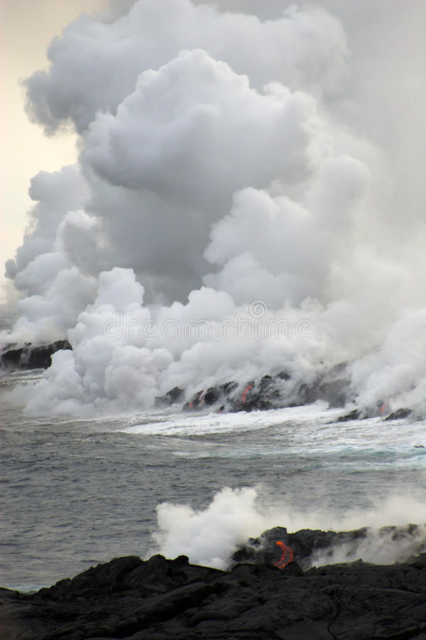 Lava flowing into the ocean. Lava erupting into Pacific Ocean during day on Big Island royalty free stock photography