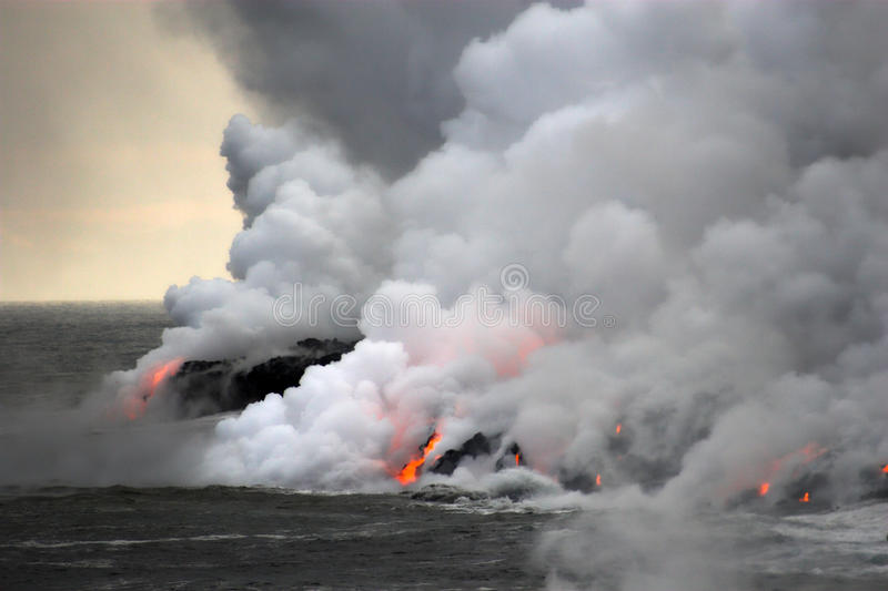 Lava flowing into the ocean. Lava erupting into Pacific Ocean during evening on Big Island royalty free stock photography