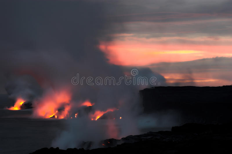 Lava flowing into the ocean. Lava erupting into Pacific Ocean at night on Big Island stock photo