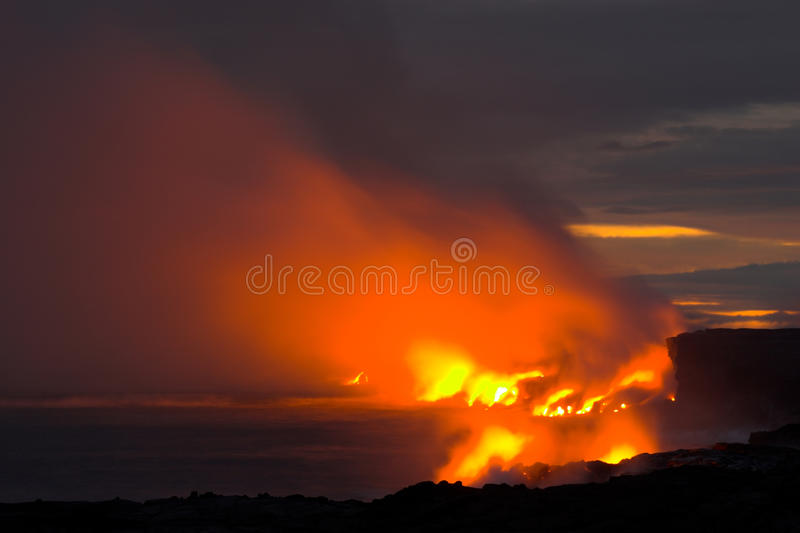 Lava flowing into the ocean. Lava erupting into Pacific Ocean at night on Big Island royalty free stock photo