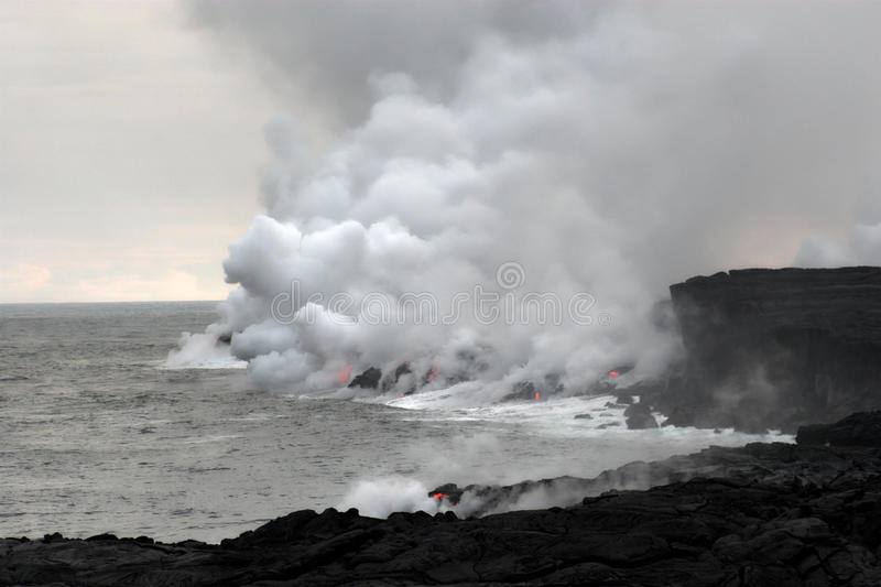 Lava flowing into the ocean. Lava erupting into Pacific Ocean during evening on Big Island stock image