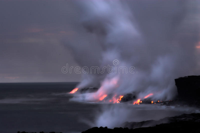 Lava flowing into the ocean. Lava erupting into Pacific Ocean at night on Big Island stock image