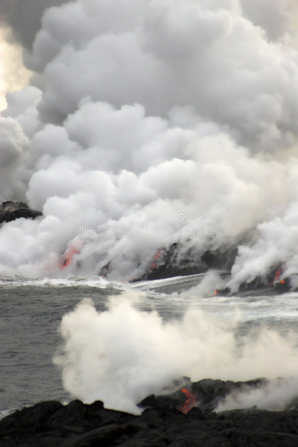 Lava flowing into the ocean. Lava erupting into Pacific Ocean during day on Big Island stock photos