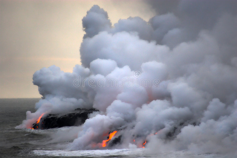 Lava flowing into the ocean. Lava erupting into Pacific Ocean during evening on Big Island stock photo