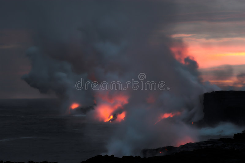 Lava flowing into the ocean. Lava erupting into Pacific Ocean at night on Big Island stock photos