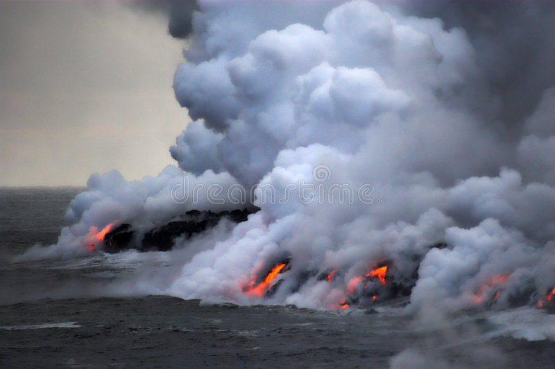 Lava flowing into the ocean. Lava erupting into Pacific Ocean during evening on Big Island stock photos