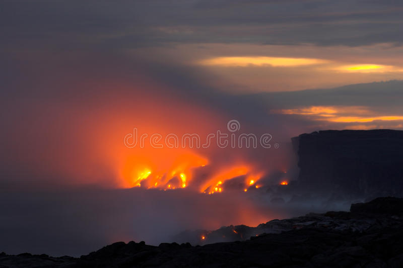 Lava flowing into the ocean. Lava erupting into Pacific Ocean at night on Big Island royalty free stock images