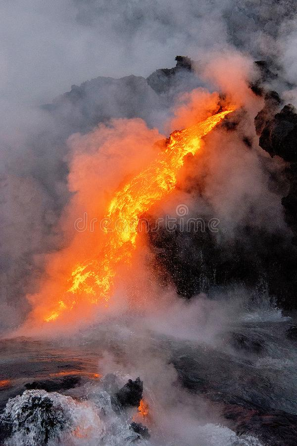 Lava flowing into the ocean in Hawaii stock images