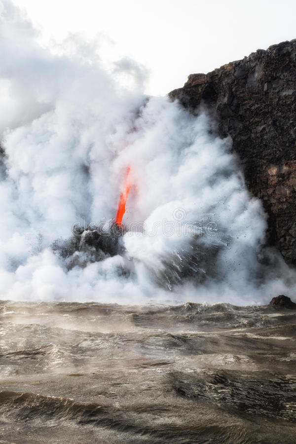 Lava flowing into ocean with steam and smoke royalty free stock image
