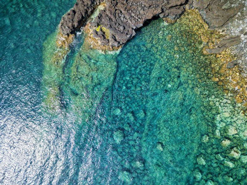Lava formation. Aerial shot of a lava formation and the beautiful blue waters of the atlantic near Canada de Africa on Sao Jorge in the Azores stock image