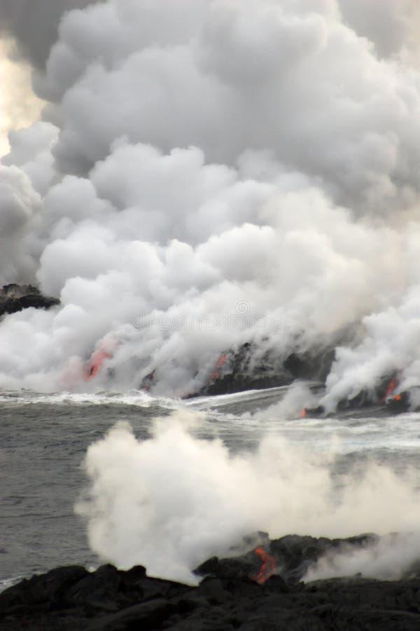 Lava que fluye en el océano fotos de archivo