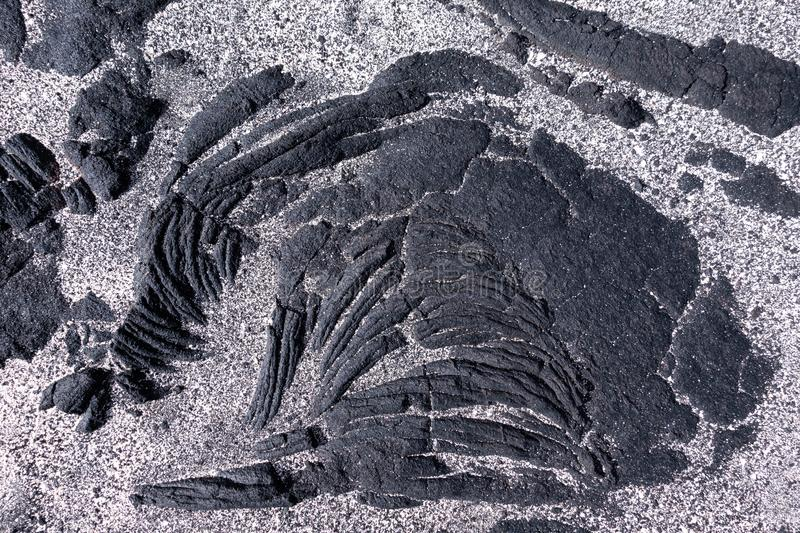 Lava with sand detail. Black, solidified pahoehoe lava partially covered with bright sand. Detail taken in El Hierro, Canary Islands, Spain stock photo