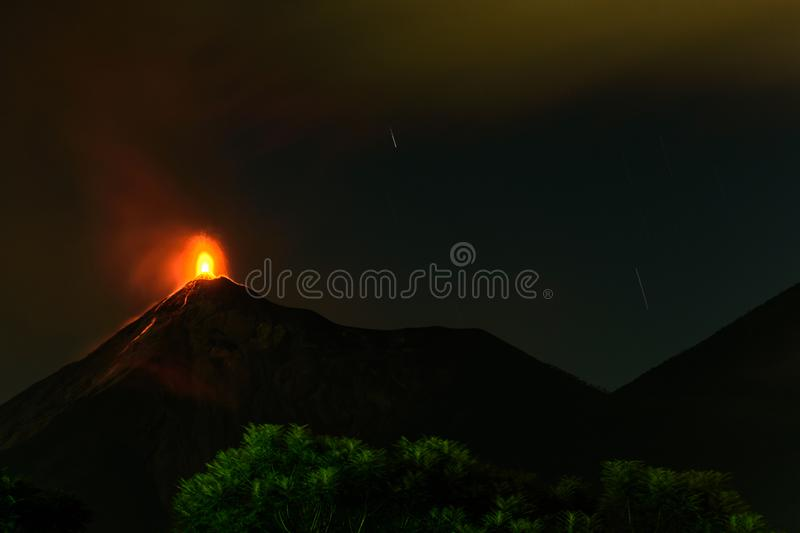 Lava spurts from erupting Fuego volcano in Guatemala. Fuego volcano erupts just after sunset next to Acatenango volcano on November 18, 2018 near Antigua stock photography