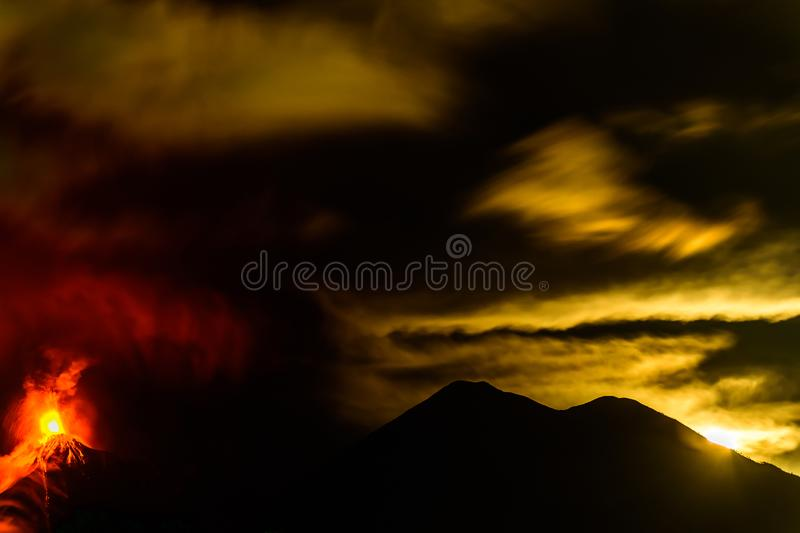 Lava spurts from erupting Fuego volcano next to Acatenango volcano in Guatemala. Fuego volcano erupts as the moon sinks behind Acatenango volcano in the early stock photos