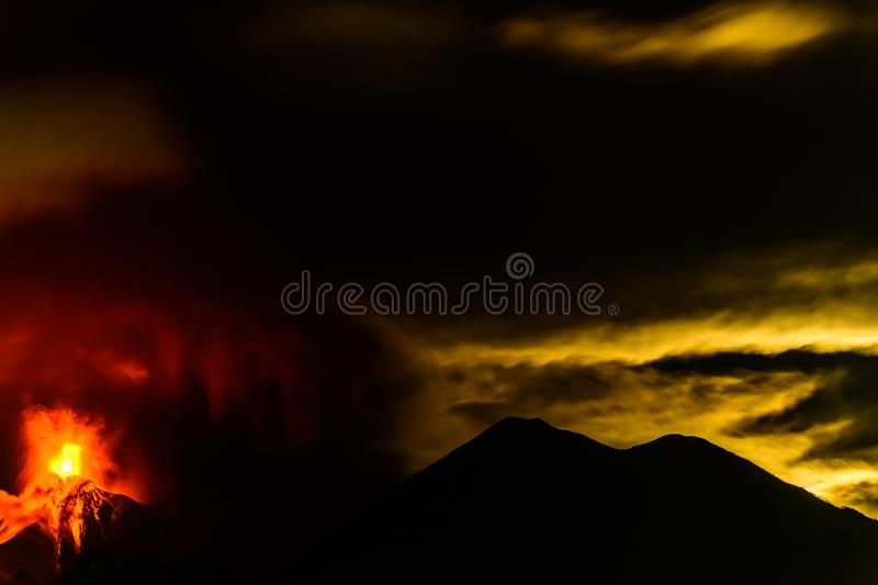 Lava spurts from erupting Fuego volcano next to Acatenango volcano in Guatemala. Fuego volcano erupts as the moon sinks behind Acatenango volcano in the early royalty free stock photography